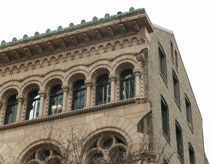 A view of the northeast corner of the Newberry's main building, where the ornate cladding is only half-complete and stone projections extend beyond the walls.