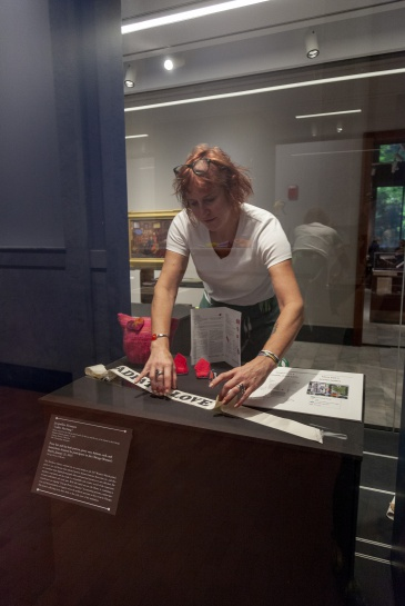 Director of Conservation Lesa Dowd installs Women's March ephemera inside a 46-foot-long display case in the Newberry's Hanson Gallery. In a single case, Newberry curators can display objects inside the gallery as well as within wall niches running along the corridor outside the gallery.