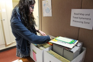 """Processing Assistant Emily Richardson at work in the """"Road Map and Travel Ephemera Processing Zone"""""""