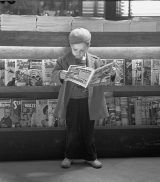 Boy reading comics in train station, Lincoln, Nebraska, 1948