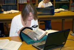 A reader studies a 16th century book in the Special Collections reading room.